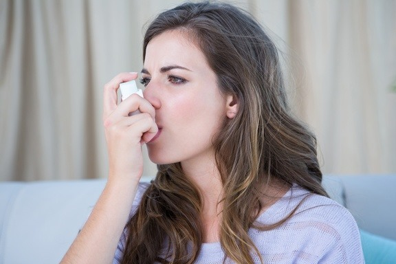 Woman Using Puffer from asthma triggers Air purifier